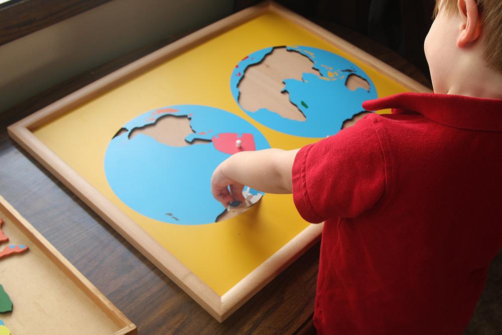 toddler doing montessori continents puzzle